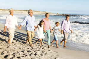 Three Generation Family Holding Hands While Walking On Beach